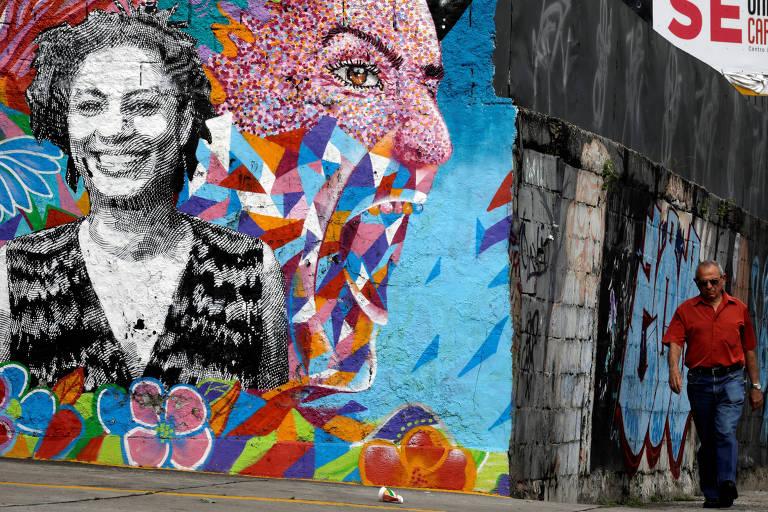 Homem passa por grafite de Marielle Franco perto do local em que a vereadora foi morta, no Rio