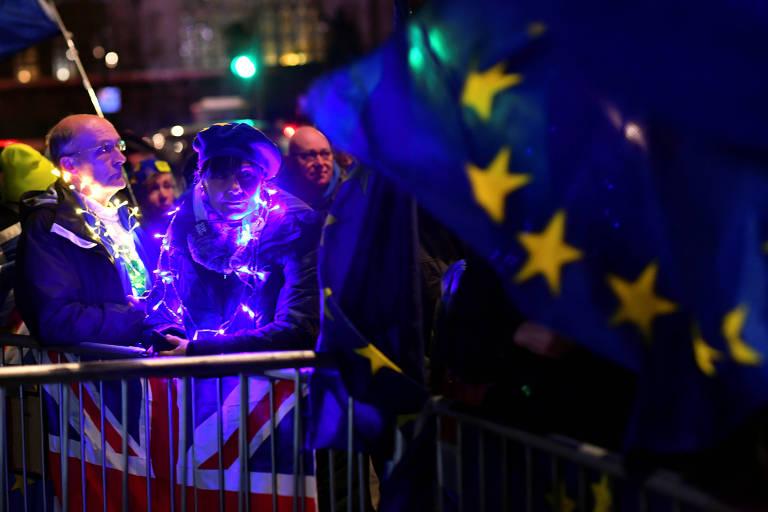 Na frenbte do Parlamento britânico, manifestantes contrários a saída do Reino Unido do bloco europeu carregam bandeiras da UE antes da votação