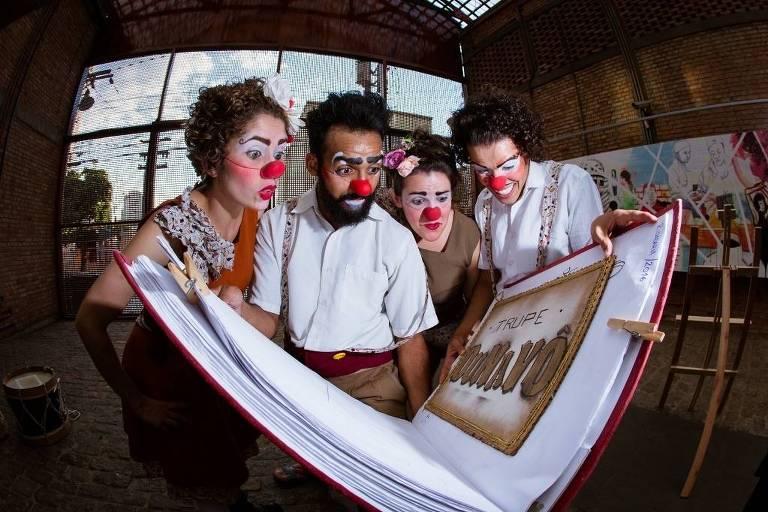quatro palhaços olham para um livro gigante