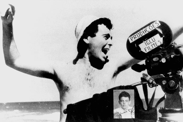 Glauber Rocha aparece sem camisa, com um chapéu, em foto em branco e preto. Ele tem a boca aberta como quem grita e gesticula com os braços levantados. Está em uma praia e com equipamentos de filmagem. É possível ver os pelos em seu peito e suas axilas.