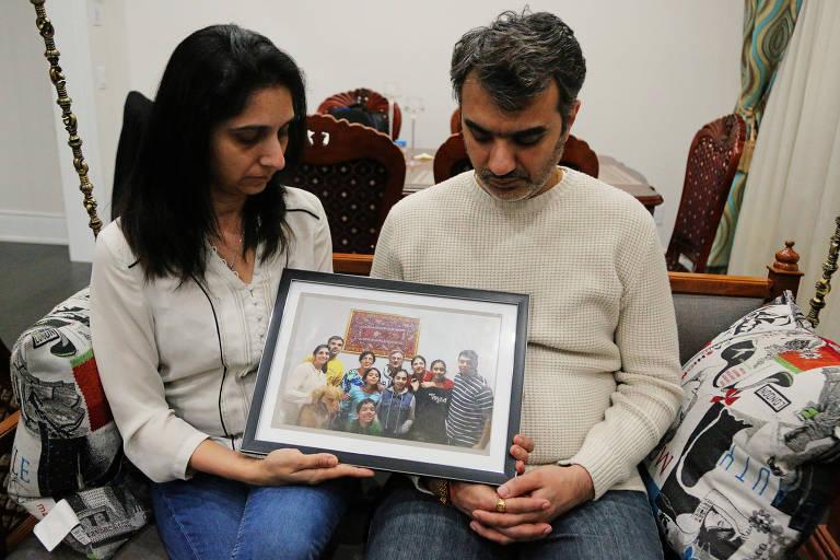 Manant e Hiral Vaidya mostram fotografia de seus familiares que estavam entre os 157 mortos do acidente com um Boeing MAX 8 da Ethiopian Airlines no domingo (10)