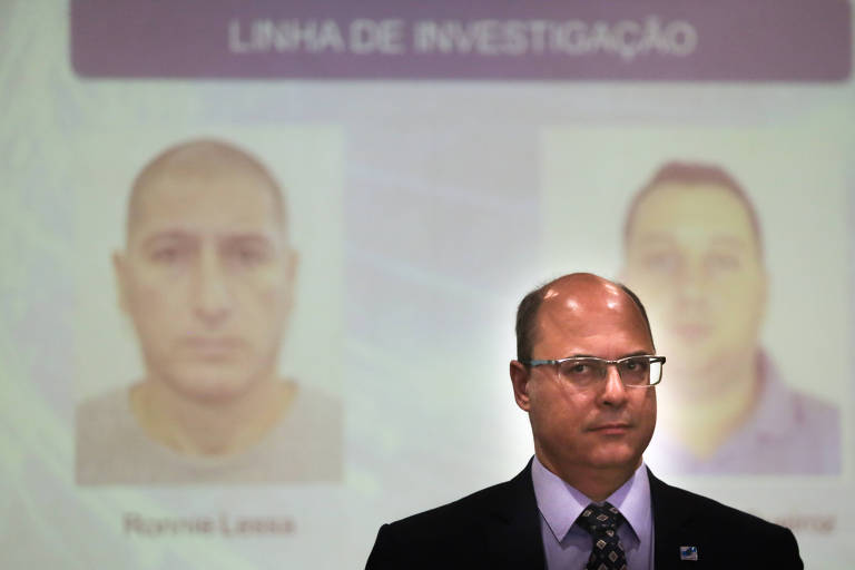 O governador do Rio de Janeiro, Wilson Witzel, em frente aos rostos dos homens suspeitos de estarem no carro que assassinou Marielle Franco