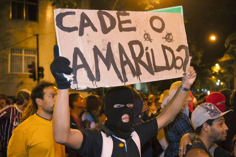 """Mascarado ergue cartaz com escrito """"Cadê o Amarildo?"""""""