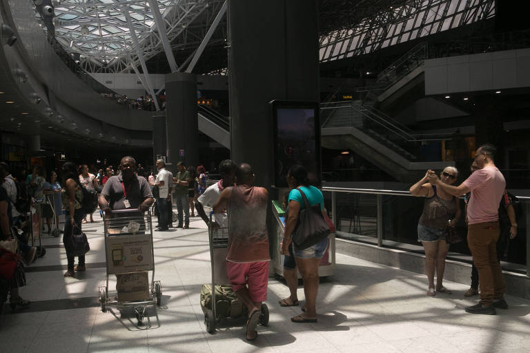 Pessoas empurram carrinhos de malas no saguão do aeroporto