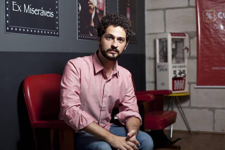 Homem de barba e cabelo preto, camisa rosa e calça jeans sentado em cadeira vermelha