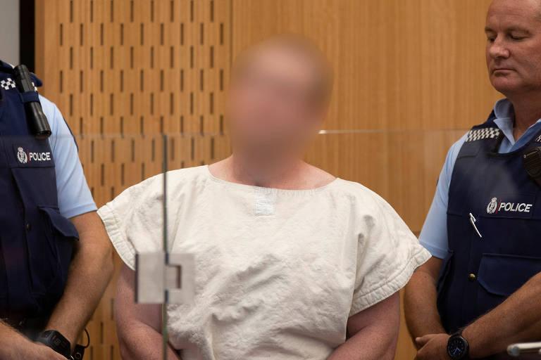 Suspeito aparece algemado e veste uniforme branco de presidiário, está ladeado por dois policiais que usam coletes a prova de balas