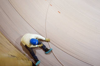 A worker sits on a giant spool of fiber-optic cable to ensure it doesn?t snag or knot on board the ship Durable in Newington, N.H.