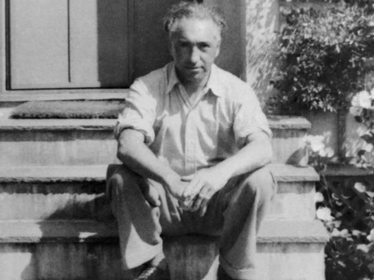 Wilhelm Reich sentado em uma escada na entrada de uma casa