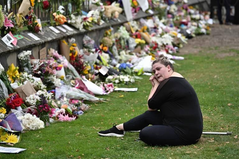Mulher observa flores deixadas na frente de hospital em Christchurch para homenagear as vítimas do massacre
