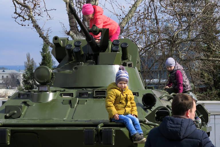 Crianças brincam sobre um blindado de transporte de tropas russo na praça Nakhimov, centro de Sebastopol