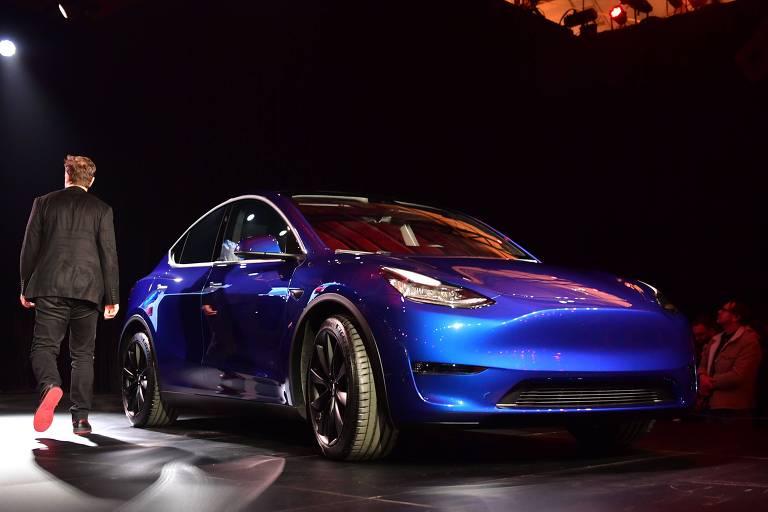 Na foto, o novo modelo do carro está parado em um palco. Ele é de cor azul brilhante. Ao lado dele, um homem