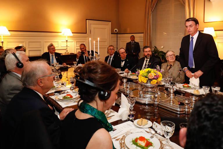 Presidente Bolsonaro discursa durante jantar em Washington, nos Estados Unidos; ao seu lado, o escritor Olavo de Carvalho