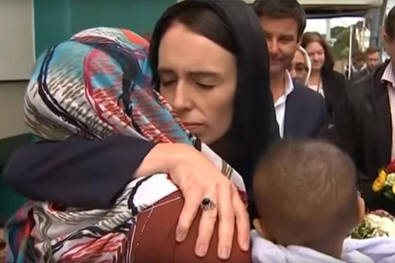 Usando um lenço preto que cobre parte da cabeça, a primeira-ministra abraça uma mulher de costas e também com a cabeça coberta