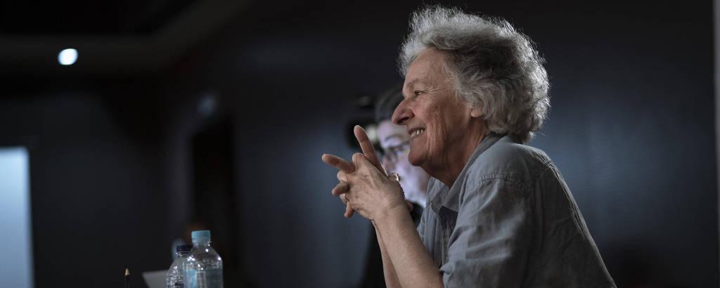 A diretora Ariane Mnouchkine está sentada, com os braços apoiados sobre uma mesa; ela sorri enquanto assiste ao ensaio