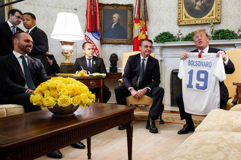 O presidente dos EUA, Donald Trump, à dir., ao lado de Jair Bolsonaro e o filho do brasileiro, à esquerda, Eduardo Bolsonaro