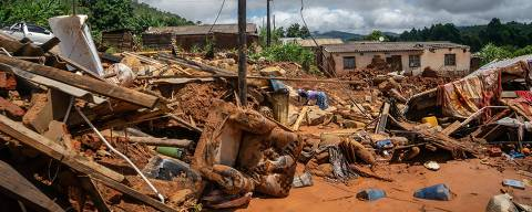 Women rummage through scattered belongings in Chiminimani on March 19, 2019, after the area was hit by the Cyclone Idai. - More than a thousand people are feared to have died in Mozambique alone while scores have been killed and more than 200 are missing in neighbouring Zimbabwe following the deadliest cyclone to hit southern Africa. Cyclone Idai tore into the centre of Mozambique on March 14 night before barreling on to neighbouring Zimbabwe, bringing flash floods and ferocious winds, and washing away roads and houses. (Photo by ZINYANGE AUNTONY / AFP)