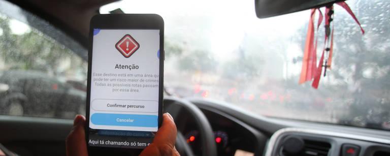 A motorista Fátima Ferreira mostra aviso de risco no aplicativo Waze