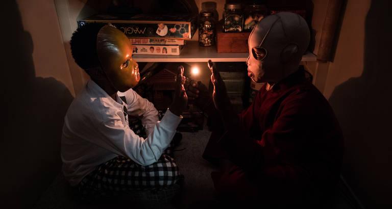 Dois meninos negros, mascarados, olhando um para o outro, enquanto carregam um palito com uma luz