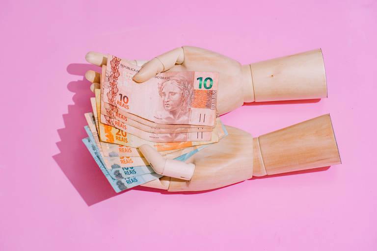 Mão de boneco segurando cédulas de real