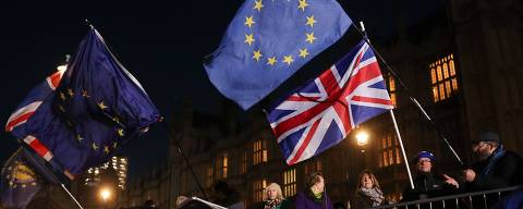 Anti-brexit campaigners wave Union and EU flags outside the Houses of Parliament in central London on December 12, 2018. - British Prime Minister Theresa May vowed to fight