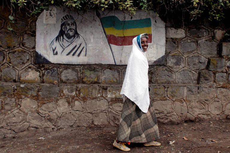 Mulher etíope caminha diante de imagem do imperador Tewodros 2º, em Addis Ababa