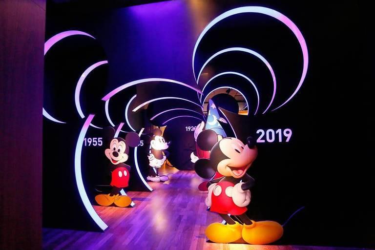 Foto mostra túnel do tempo com diferentes desenhos do personagem Mickey, da Disney, ao longo dos anos