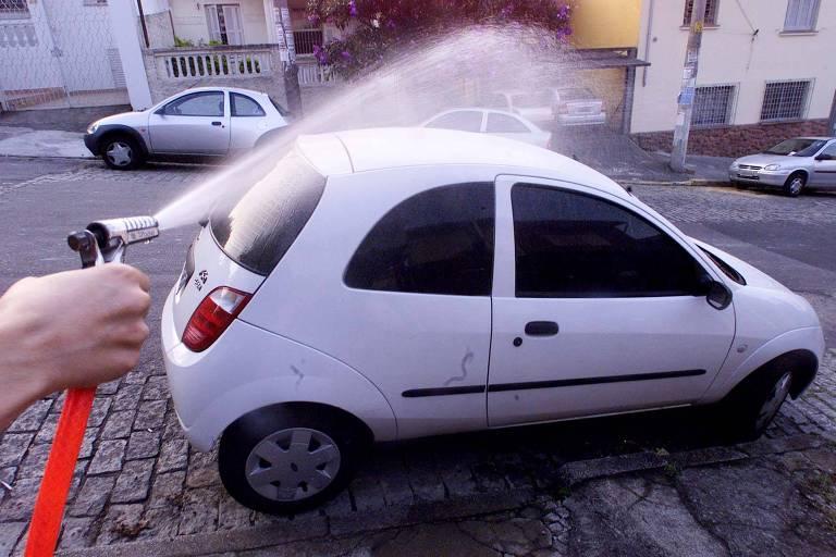 Homem lava carro com mangueira