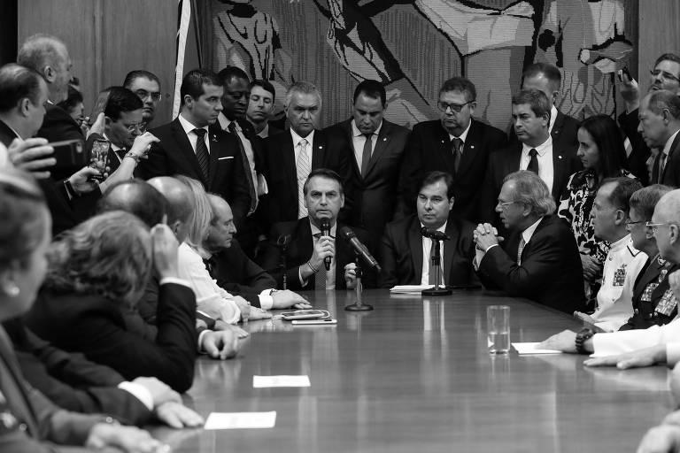 Jair Bolsonaro, no centro, durante a entrega da proposta de reforma da Previdência para militares para o presidente da Câmara, Rodrigo Maia
