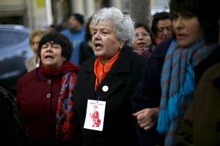 De Negri, Quintana, and Lira, shout slogans before delivering a letter to Chile's President Bachelet to demand justice outside the government palace in Santiago