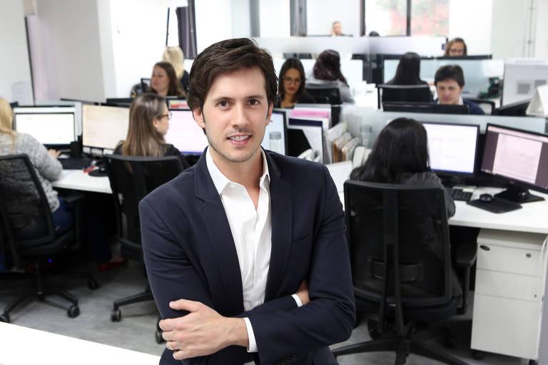Homem branco de terno em frente a sala com computadores