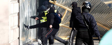 Protesters demolish a shop window of a luxury store during a demonstration by the