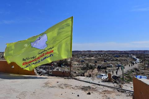 A picture taken on March 23, 2019 shows the US-backed Syrian Democratic Forces' (SDF) flag atop a building in the Islamic State group's last bastion in the eastern Syrian village of Baghuz after defeating the jihadist group. - The Kurdish-led forces pronounced the death of the Islamic State group's nearly five-year-old