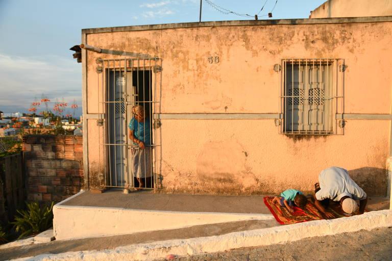 O auxiliar de pedreiro, Valdeiton Conceição Santos, 30, ensina o filho Lucas Santos, 2 a rezar em direção a Meca