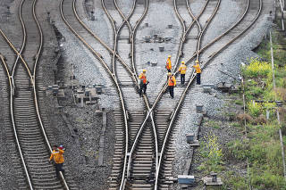 Workers inspect railway tracks, which serve as a part of the Belt and Road freight rail route linking Chongqing to Duisburg, at Dazhou railway station