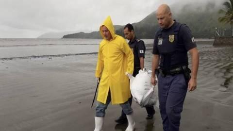 Homens carregam corpo de cachorro enforcado em São Sebastião, no litoral de SP