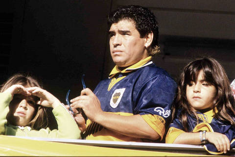 Futebol: o jogador Diego Maradona assiste jogo do Boca Juniors com suas filhas: Veteran soccer star Diego Maradona, flanked by his daughters Giannina [L] and Dalma, observes his team  Boca Juniors  play Independiente in a match for the Argentine league November 3. Maradona, who has not  played in the last few months, claims to be emotionally hurt not only by his manager's Guillermo Coppola imprisonment on drug-trafficking charges but also by   the misfortunes of his beloved Boca Juniors in the current championship. Boca Juniors lost 1-0.                     em/Photo by Enrique Marcarian  REUTERS*** NÃO UTILIZAR SEM ANTES CHECAR CRÉDITO E LEGENDA***