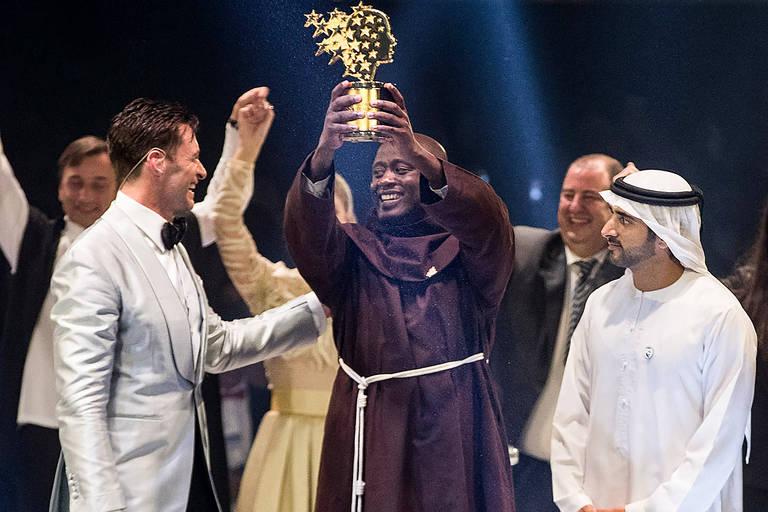 Peter Tabichi recebe o prêmio ao lado do ator Hugh Jackman e do príncipe Hamdan bin Mohammed Al-Maktoum