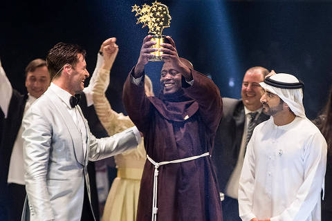 This handout picture provided on March 24, 2019 by the Global Education and Skills Forum, an initiative of the Varkey Foundation, shows Kenyan teacher Peter Tabichi (C) holding up the Global Teacher Prize (GTP) trophy after winning the US$ 1 million award during an official ceremony in Dubai presented by Australian actor Hugh Jackman (C-L) and attended by the Dubai Crown Prince Hamdan bin Mohammed Al-Maktoum (C-R). - Tabichi, a 36-year-old maths and physics teacher at Keriko Secondary School in the village of Pwani, in Kenya's Nakuru county, was named as winner of the