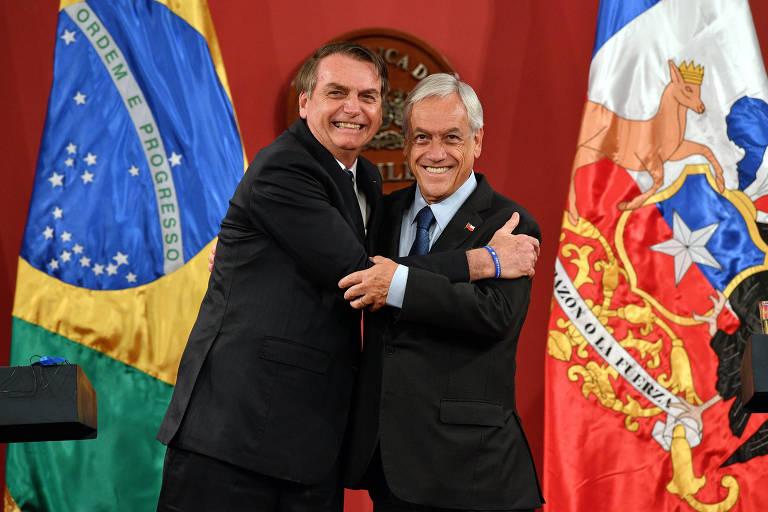 O presidente Jair Bolsonaro abraça o presidente do Chile,  Sebastián Piñera, durante encontro no sábado (23), no palácio de La Moneda