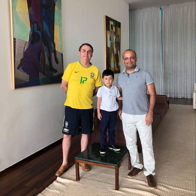 Na foto, presidente está a esquerda e usa camiseta da seleção brasileira e bermuda. No meio, o filho do deputado está em pé sobre uma mesinha. E à direita, major Vitor, que usa camiseta polo e calça clara. Ele está com o braço ao redor dos ombros da criança