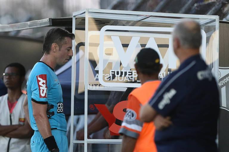 O árbitro Raphael Claus, no jogo entre Palmeiras e Novorizontino, observa lance no VAR, durante partida valida pelas quartas de final (ida), do Campeonato Paulista, Série A1, no Estádio Jorge Ismael de Biasi.