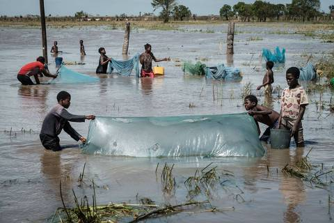 TOPSHOT - People use nets to fish in a flooded area hit by the Cyclone Idai near Tica, Mozambique, on March 24, 2019. - Cyclone Idai smashed into Mozambique's coast unleashing hurricane-force wind and rain that flooded swathes of the poor country before battering eastern Zimbabwe -- killing 705 people across the two nations. (Photo by Yasuyoshi CHIBA / AFP)