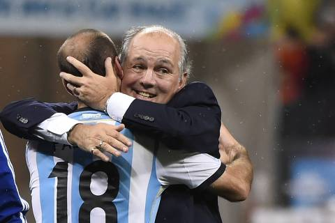 Argentina's forward Rodrigo Palacio (L) and Argentina's coach Alejandro Sabella hug after winning their FIFA World Cup semi-final match against the Netherlands in a penalty shoot-out following extra time at The Corinthians Arena in Sao Paulo on July 9, 2014.  AFP PHOTO / FABRICE COFFRINI ORG XMIT: 3866