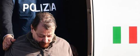 (FILES) In this file photo taken on January 14, 2019 Italian former communist militant Cesare Battisti, wanted in Rome for four murders attributed to a far-left group in the 1970s, is escorted by an Italian Police officer as he steps off a plane coming from Bolivia and chartered by Italian authorities, after landing at Ciampino airport in Rome. - Former communist militant Cesare Battisti, who is serving a life sentence in Italy over four murders carried out in the 1970s, has confessed to the deaths after always denying responsibility, media reported on March 25, 2019. (Photo by Alberto PIZZOLI / AFP)