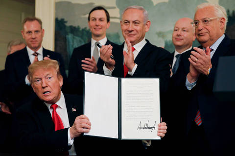 U.S. President Donald Trump holds a proclamation recognizing Israel's sovereignty over the Golan Heights as he is applauded by Israel's Prime Minister Benjamin Netanyahu and others during a ceremony in the Diplomatic Reception Room at the White House in Washington, U.S., March 25, 2019. REUTERS/Carlos Barria     TPX IMAGES OF THE DAY ORG XMIT: WAS112