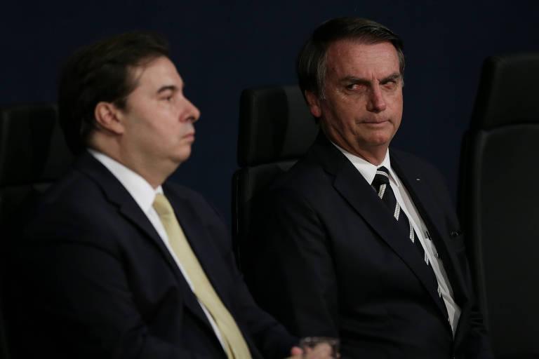 O presidente Jair Bolsonaro (ao fundo) participa de solenidade ao lado do presidente da Câmara, Rodrigo Maia