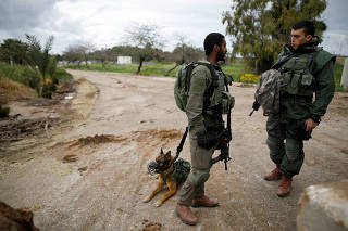 Israeli soldiers stand with a sniffer dog near the border with Gaza, in southern Israel