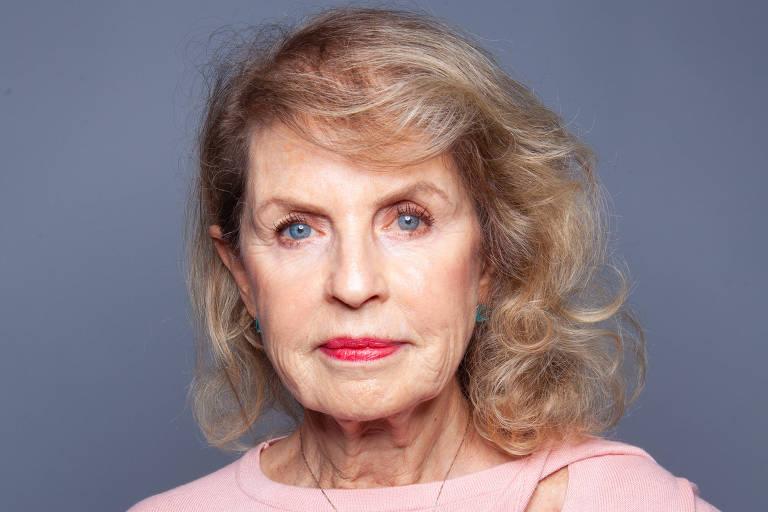 Mulher idosa, de cabelos loiros e olhos azuis, posa olhando para a câmera, usando um suéter rosa, com a mão na cintura