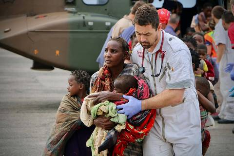 TOPSHOT - People are escorted to safety by aid workers at the airport of the coastal city of Beira in central Mozambique on March 19, 2019, after the area was hit by the Cyclone Idai. - More than 80 people were rescued by Rescue South Africa and the South African army with helicopters from the Buzi area, province of Safala, where they were stranded since March 15. Rescue workers in Mozambique were racing against time to pluck people off trees and rooftops on March 19, after a monster storm reaped a feared harvest of more than 1,000 lives before smashing into Zimbabwe. Four days after Tropical Cyclone Idai made landfall, torrential rains and powerful winds, combined with flash floods that have swept away roads and bridges, inflicted further pain on the two impoverished countries. (Photo by ADRIEN BARBIER / AFP)