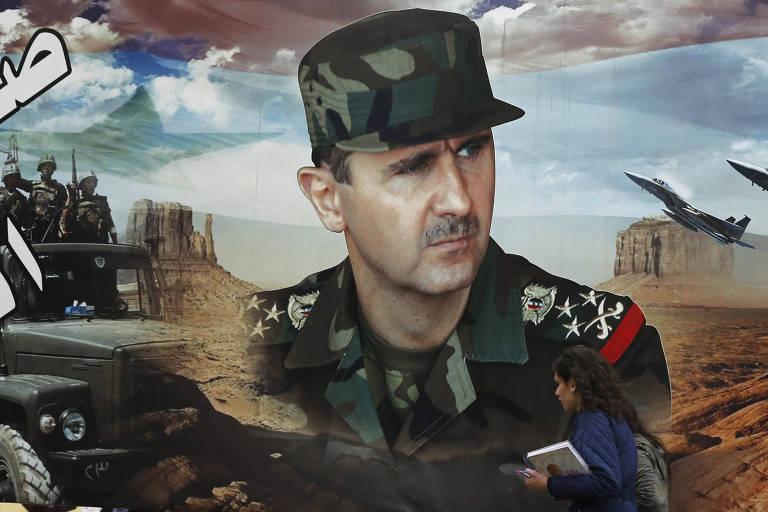 Mulher passa em frente a retrato de Bashar al-Assad em Damasco